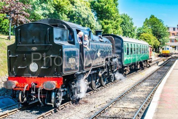 Swanage, England 3rd July 2011 Swanage Rail – Steam Engine Black train with co​nversation between driver and guard - Photo Walk UK