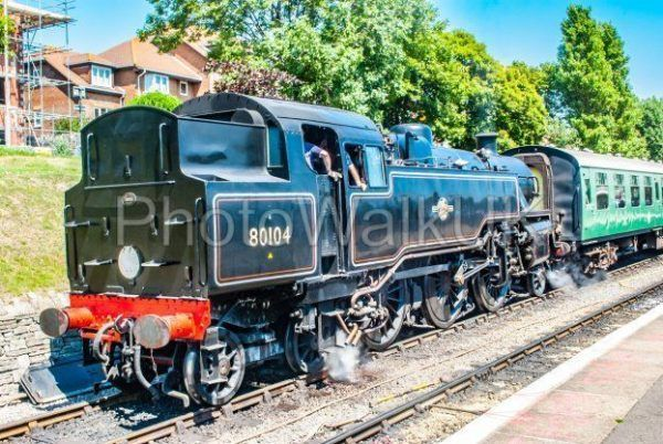 Swanage, England 3rd July 2011 Swanage Rail. Steam Engine Black train with co​nversation between driver and guard - Photo Walk UK
