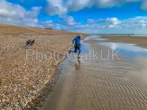 Woman Running on Beach with Young Poodle - Photo Walk UK