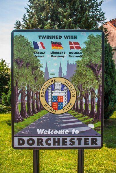 Welcome to Dorset Town Sign showing twinned cities Bayeux, Lubbecke and Holbaek - Photo Walk UK